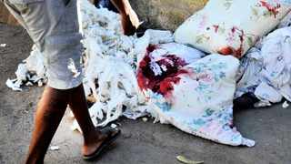 02/06/2014. A family member looks at bloodstained blankets that had covered a police officer who shot and killed himself after shooting his girlfriend. Picture: Thobile Mathonsi
