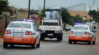 1/21/15 JMPD officers escorts Foreign shops owners with their belongings out of Braamfischer, Soweto yesterday moments community members looted the shop. The looting of shops owned by Pakistanis is spreading quickly in Soweto after a 16 year-old was killed by a Pakistan shop owner this week in Snake Park,Soweto. Picture:Paballo Thekiso
