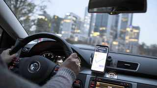 A DASHBOARD-mounted smartphone displays the Uber app on a ride in Frankfurt, Germany.