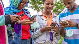 A GROUP of young people using their mobile phones.