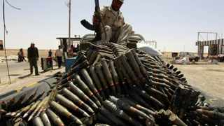 A Libyan rebel fighter sits atop a pick-up truck loaded with anti-aircraft ammunition.