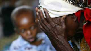A Malawian grandmother rests in 2005, close to her malnoureshed grandson in the Zomba NRU (Nutritional and Rehabilitation Unit). Picture: Gianluigi Guercia