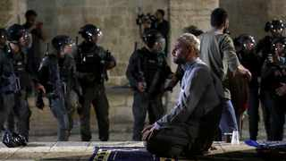 A Palestinian man prays as Israeli police gather during clashes at the compound that houses Al-Aqsa Mosque, known to Muslims as Noble Sanctuary and to Jews as Temple Mount, amid tension over the possible eviction of several Palestinian families from homes on land claimed by Jewish settlers in the Sheikh Jarrah neighbourhood, in Jerusalem's Old City. Picture: Ammar Awad/Reuters