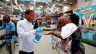 A STORE assistant gives people hand sanitiser as shoppers stock up on groceries at a Makro Store ahead of a nationwide 21-day lockdown in an attempt to contain the Covid-19 outbreak in Durban.