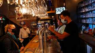 A bartender, wearing a face mask to fight against the spread of the coronavirus. File picture: Francisco Seco/AP