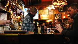 A bartender wearing a face mask works while people drink and socialise in a pub. Picture: Reuters