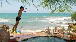A boy dives into a swimming pool at Jake's Place hotel on Treasure Beach, Jamaica. Picture: AP
