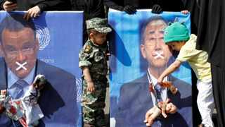 A boy holds a toy against a defaced poster of the UN Secretary-General Ban Ki-moon during a protest against Saudi-led air strikes in Sanaa, Yemen. Picture: Mohammed Sayaghi/Reuters