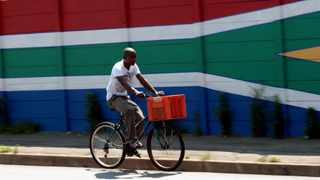 A cyclist rides past a South African flag painted on a wall in downtown Johannesburg. FILE IMAGE.