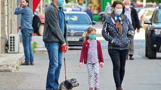A family walking their dog while wearing masks against the spread of Covid-19. File picture: Candid Shots/Pixabay