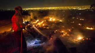 A firefighter tackles the blaze raging in Tokai Forest on Tuesday. Picture: Nic Bothma