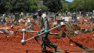 A funeral worker walks carrying a casket lowering device after a burial at the Westpark Cemetery, amid the coronavirus disease outbreak. Picture: Siphiwe Sibeko/Reuters