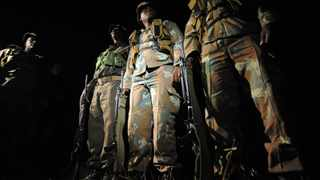 A group of SANDF soldiers listen to their platoon commander as they prepare to go out on a night patrol in Kruger National Park. File picture: Phill Magakoe