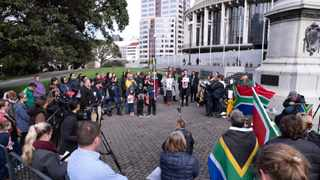 A group of South African expatriates protest outside the New Zeland parliament to high light the plight of their homeland as well as to call on the New Zealand government to speed up the immigration process for their relatives still in South Africa, and provide aid those affected by the rioting and looting. Picture: Giordano Stolley