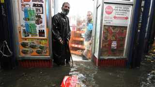 A homeless man stands in the doorway of a deli during flash flooding caused by storm Ida in the New York City borough of Queens. Picture: Anthony Behar/Sipa USA
