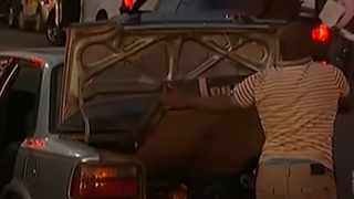 A looter tries to get a 54-inch TV into the boot of his car.