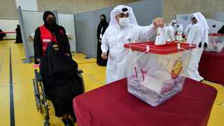 A man casts a ballot as a woman in a wheelchair looks on during the Gulf Arab state's first legislative elections for two-thirds of the advisory Shura Council, in Doha, Qatar. Picture: Reuters/Nooman Ben Amor