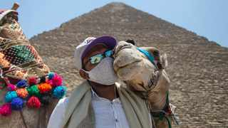 A man holds a camel in front of the Giza Pyramids after the place was reopened for tourist visits in Giza. Picture: EPA