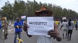 """A man holds a placard with a play on words referring to the Congolese president and reading """"Sassou enough"""" during an opposition demonstration in Brazzaville on September 27, 2015. Picture: Laudes Martial Mbon"""