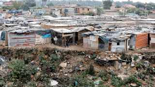 A man picks his way between closely packed shacks in Alexandra. Picture: Siphiwe Sibeko/ Reuters