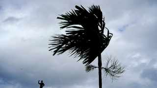 A man stands on a store's roof as he works to prepare it for the arrival of Hurricane Dorian in Freeport on Grand Bahama, Bahamas Picture: AP Photo/Ramon Espinosa