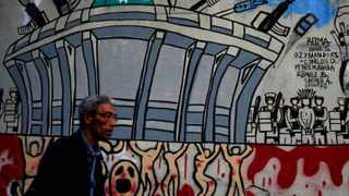A man walks next to a mural against the World Cup painted on a wall in Rio de Janeiro.