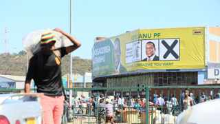A man walks past a poster of Zanu-PF leader Emmerson Mnangagwa in Harare yesterday. Zimbabweans will go to the polls on Monday to elect new members of parliament and the president. Picture: Aaron Ufumeli/EPA-EFE