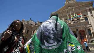 A man wearing a Nelson Mandela printed cloth stands in front of the City Hall in Cape Town as he joins along with others to write condolences in a book for Mandela. REUTERS/Mark Wessels