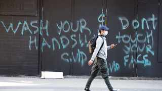 """A man wearing a protective face mask walks past a spray painted wall saying """"Wash your hands and don't touch your face"""" Wednesday, March 18, 2020, in in downtown Vancouver, British Columbia. (Jonathan Hayward/The Canadian Press via AP)"""