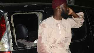 A man who survived the drive-by shooting of Muslim cleric Sheikh Ibrahim Ismail is seen next to a bullet-riddled car on the Mombasa-Malindi highway on October 3, 2013. File photo: AFP