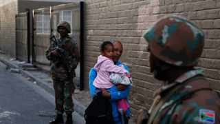 A man with his child walks between two SANDF soldiers as they provide security for Policemen during a raid in Manenberg in 2015. File photo: AP Photo/Schalk van Zuydam.