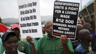 A member of the Association of Mineworkers and Construction Union (Amcu) holds placards as he attends a protest march.