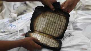 A partially burnt copy of Qur'an is seen next to dead members of the Muslim Brotherhood and supporters of Morsi at El Eyman mosque in Cairo .