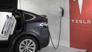 A plug sits connected to a Tesla Inc. Model X electric automobile at a charging point in a parking lot in Frankfurt, Germany, on Friday, Aug. 11, 2017. Photographer: Alex Kraus/Bloomberg