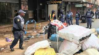A police officer walks past bags of counterfeit goods that were seized in raids carried out by the SAPS and the Joburg metro police in the city's CBD yesterday. File photo: Bhekikhaya Mabaso African News Agency (ANA).