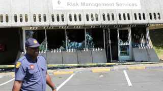 A policeman walks past the ruins of the Risk Management Services building at the Westville campus that was burnt by protesting students early Wednesday. Picture: Motshwari Mofokeng / African News Agency / ANA