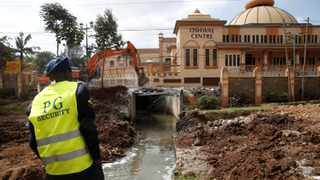 A private security officer stands guard as heavy machinery demolishes a bridge near the Oshwal Centre in Westlands, Nairobi, Kenya, this week. Picture : Baz Ratner/Reuters