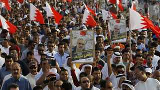 A protester carries a banner with photo of political prisoner Ebrahim Shareef, as he participates in an anti-government rally organised by Bahrain's main opposition group Al Wefaq, in the village of Salmabad south of Manama, April 12, 2013. REUTERS/Hamad I Mohammed