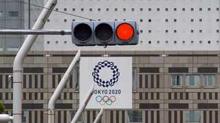 A red traffic light lights up on a street near the Tokyo Metropolitan Government Building displaying a banners of Tokyo 2020 Olympics Games in Tokyo. Photo: Kazuhiro Nogi/AFP