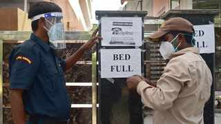 A security guard puts up a notice informing the non-availability of beds for patients in a private hospital amid Covid-19 coronavirus pandemic in Allahabad. Picture: Sanjay Kanojia/AFP