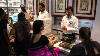 A shop manager (2nd R) speaking with customers at a jewellery shop in Mumbai. Photo by Punit Paranjpe/AFP