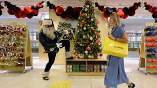 A shopper walks past an actor dressed as Rock and Roll Santa, at the launch of the Christmas shop at Selfridges store in London. Picture: Kirsty O'Connor/PA via AP