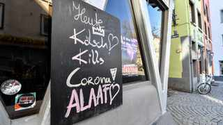 """A sign at a closed pub reads """"Koelsch kills Corona! Alaaf"""" in the old town of Cologne, Germany, Tuesday, March 17, 2020. The city closed all bars and restaurants due to the coronavirus outbreak. Koelsch is a local beer product. All public and private events are banned. (AP Photo/Martin Meissner)"""