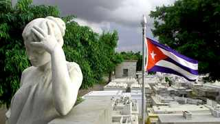 A statue and a Cuban flag near the grave of the Cuban politician Eduardo Chibas, a crusader against corruption who committed suicide in 1951. A Cuban living in South Africa lifts the lid on life inside Cuba, and talks about the growing pro-democracy movement happening around the world. Picture: Cristobal Colon Necropolis, Cuba tourism, graveyards