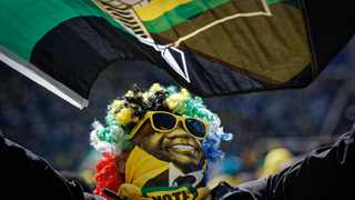 A supporter of the ruling African National Congress (ANC) wears a mask of President Cyril Ramaphosa and waves the party flag as he attends their final election rally at Ellis Park stadium in Johannesburg in 2019 Picture: AP Photo/Ben Curtis