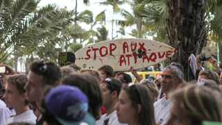 """A surfboard with the message """"Stop the attacks"""" is seen during a demonstration attended by 300 people near the prefecture in Saint Denis on the Indian Ocean island of Reunion."""