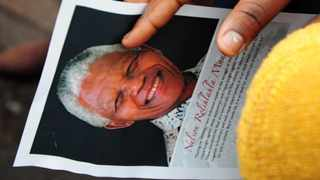 A woman holds a portrait of late former South African president Nelson Mandela as she attends the retransmission of the memorial service for Mandela, in front of the city hall in Durban. AFP PHOTO / Anesh Debiky