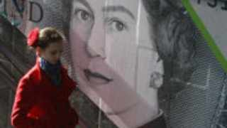 A woman passes by an outdoor advert with an image of the British pound bank note.