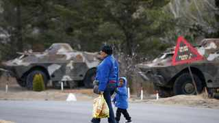 A woman walks with a child past armed personnel carriers at the entrance of the army barracks in Maseru. REUTERS/Siphiwe Sibeko