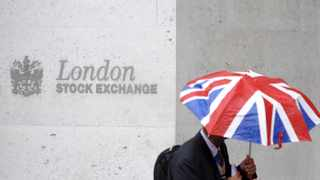 A worker shelters from the rain under an umbrella as he passes the London Stock Exchange in the City of London. File picture: Toby Melville